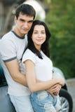 Par som plattforer utanför deras bil i omfamning Fotografering för Bildbyråer