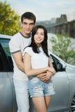 Par som plattforer utanför deras bil i omfamning Royaltyfri Bild