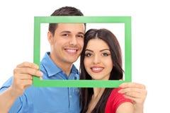 Par som poserar bak en grön bildram Arkivbilder