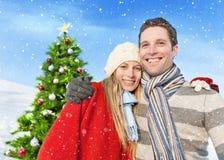 Par som poserar i det fria i Front Of Christmas Tree Arkivbild