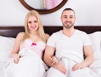 Par som poserar i säng Royaltyfri Foto