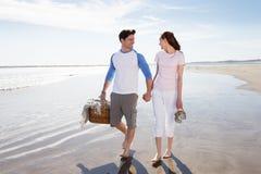 Par som promenerar stranden med picknickkorgen Arkivfoton