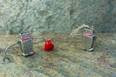 Par som är förälskade av robotar med en hjärta Begrepp för St-valentindag Arkivfoto