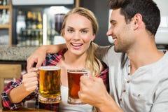 Par som rostar med öl Arkivfoto
