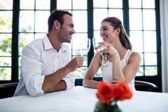 Par som rostar vinexponeringsglas på att äta middag tabellen Royaltyfri Bild