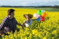 Par som rymmer färgrika ballonger i senapsgult fält arkivbilder