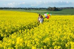 Par som rymmer färgrika ballonger i senapsgult fält arkivfoto