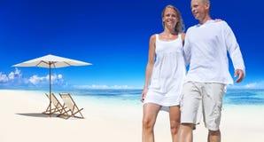 Par som rymmer sig som går vid stranden royaltyfria foton