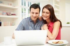 Par som ser bärbara datorn över frukosten Arkivfoton