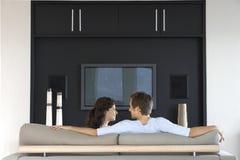 Par som ser de, medan koppla av på soffan royaltyfri foto