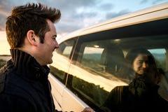 Par som ser de till och med bilfönstret Lyckliga pojkvänner som ler och royaltyfri fotografi