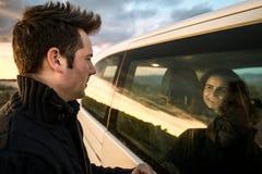 Par som ser de till och med bilfönstret Lyckliga pojkvänner som ler och royaltyfria bilder