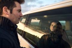 Par som ser de till och med bilfönstret Lyckliga pojkvänner som ler och arkivfoto