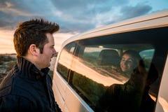 Par som ser de till och med bilfönstret Lyckliga pojkvänner som ler och arkivbilder
