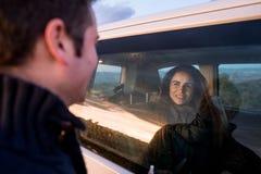 Par som ser de till och med bilfönstret Lyckliga pojkvänner som ler och royaltyfri foto