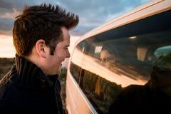 Par som ser de till och med bilfönstret Lyckliga pojkvänner som ler och arkivfoton