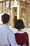 Par som ser den oavslutade husstrukturen Arkivfoton