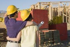 Par som ser den oavslutade husstrukturen Arkivbild