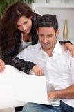 Par som ser en bärbar dator Arkivbild