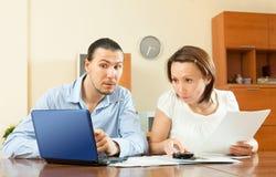Par som ser finansiella dokument i bärbar dator royaltyfria foton