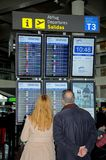 Par som ser information om flyg, Malaga. Fotografering för Bildbyråer