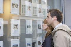 Par som ser skärm på det Real Estate kontoret royaltyfria bilder