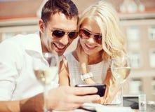 Par som ser smartphonen i kafé Royaltyfri Fotografi