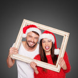 Par som ser till och med bärande jultomtenhattar för ram arkivfoto