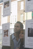 Par som ser till och med fönster på fastighetsmäklare Royaltyfri Foto