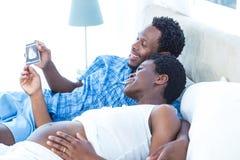 Par som ser ultraljudsundersökning, medan koppla av Royaltyfri Foto