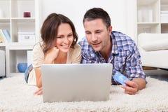 Par som shoppar direktanslutet genom att använda bärbara datorn och kreditkorten Arkivfoton