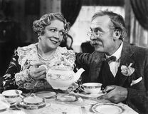 Par som sitter ha tillsammans te (alla visade personer inte är längre uppehälle, och inget gods finns Leverantörgarantier som Arkivfoto