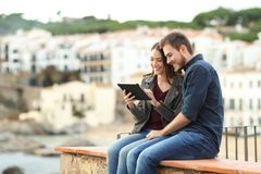 Par som sitter på en avsats genom att använda en minnestavla på semester arkivfoto