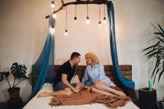 Par som sitter på säng i det stilfulla dekorerade sovrummet som ser framsidan - - framsida arkivfoto