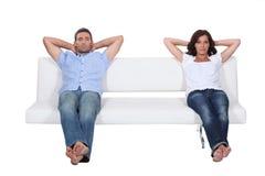 Par som sitter på sofaen Arkivfoton
