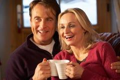 Par som sitter på sofaen med varma drinkar som håller ögonen på TV:N Royaltyfri Foto