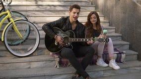 Par som sitter på trappan som spelar gitarren och tillsammans sjunger sång Man i svart tillfällig spela gitarr, medan sitta lager videofilmer