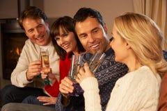 Par som sitter på sofaen med champagne Arkivfoto