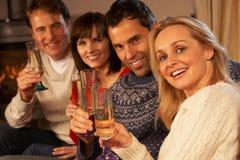 Par som sitter på sofaen med champagne Royaltyfri Bild