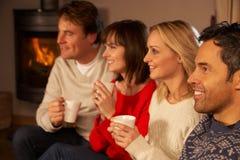 Par som sitter på sofaen med den varma drinkWathing TV:N Royaltyfri Fotografi