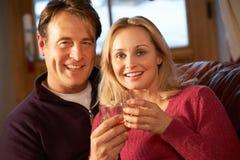 Par som sitter på sofaen med exponeringsglas av Whisky Arkivbilder