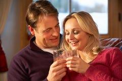 Par som sitter på sofaen med exponeringsglas av Whisky Royaltyfria Bilder