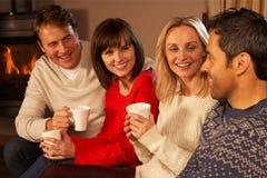 Par som sitter på sofaen med varmt drinksamtal Arkivfoton