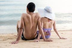 Par som sitter tillsammans att koppla av på paradisstranden Royaltyfri Foto