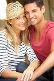 Par som sitter utanför hus Fotografering för Bildbyråer