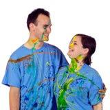 Par som skrattar ha after ett målarfärgslagsmål Arkivfoto