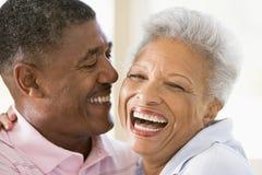 par som skrattar inomhus att koppla av royaltyfri foto
