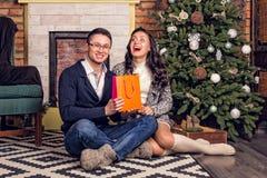 Par som skrattar med överraskningjulklapp Arkivbild