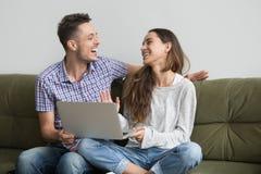 Par som skrattar, når att ha hållit ögonen på den roliga videoen Royaltyfri Foto