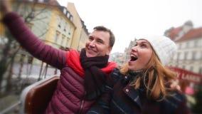 Par som skrattar och har gyckel i den ganska julen Vänner under vinterferie i karusellen eller karusell på lager videofilmer